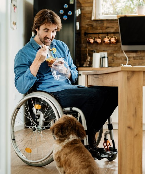 man in wheelchair feeding his dog